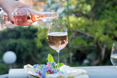 Waiter pouring a glas of cold rose wine, outdoor terrase, sunny. Day, green garden background Stock Photography