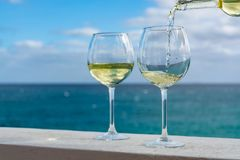 Waiter pouring glass of white wine on outdoor terrace with sea v. Waiter pouring glass of white wine on outdoor terrace with beautiful romantic sea view Stock Images