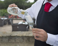 Waiter pouring a glass of  wine or champagne outside Royalty Free Stock Photo