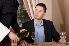 Waiter pouring a glass of wine Stock Photography