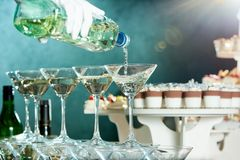 Waiter is pouring martini in glasses on the catering background. Waiter is pouring martini in polished glasses on the restaurant s catering background with Royalty Free Stock Photos