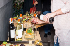 Waiter pouring red wine in a glass at a restaurant table full of appetizers with guests standing near. Royalty Free Stock Photos