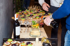 Waiter pouring red wine in a glass at a restaurant table full of appetizers with guests standing near. Royalty Free Stock Images