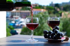 Waiter pouring red wine on outdoor cafe terrace. In sunny summer day in France stock photo