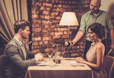 Waiter pouring sparkling wine into glasses Stock Photography