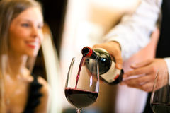 Waiter pouring wine. Waiter serving red wine to a beautiful woman in a restaurant Royalty Free Stock Photo