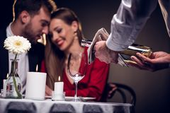 Waiter pouring wine while beautiful couple having romantic date in restaurant. On valentines day royalty free stock image