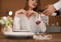Waiter pouring wine into glass for client at restaurant. Waiter pouring wine into glass for beautiful women at restaurant Stock Image
