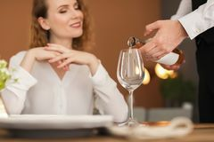 Waiter pouring wine into glass for client. At restaurant Stock Images