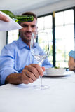 Waiter pouring wine in a glass of costumer. Sitting at restaurant stock images