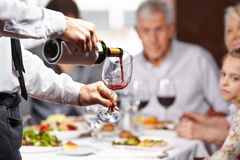 Waiter pouring wine in glass Stock Photo