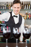 Waiter pouring wine into glasses Stock Photos