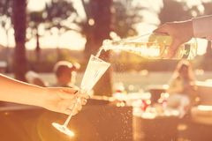 Waiter is pourring sparkling wine into a woman glass at the outd. Oor party.  Celebration concept. Event, party, wedding background. Toned image. Horizontal Royalty Free Stock Image