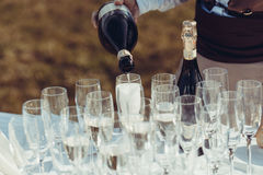 Waiter pours champagne in glasses stock images