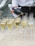 The waiter pours champagne into glasses Royalty Free Stock Image