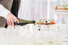 Waiter pours champagne in glasses stock photography