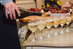The waiter pours champagne. On the buffet table. Sparkling wine at the party Stock Photos