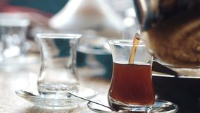 The waiter pours the eastern tea in cups stock video