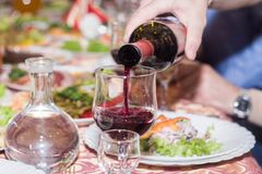 Red wine poured into a glass royalty free stock image