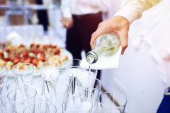 Waiter pours white wine in wineglass. Hand of the waiter pours white wine in wineglass. Bright picture of pouring wine into glasses Royalty Free Stock Image