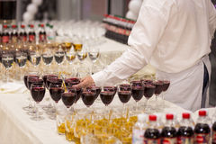 The waiter pours wine into a glass.glasses on the white table, A Royalty Free Stock Photo
