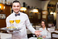 Waiter with prepared meal at table Royalty Free Stock Image