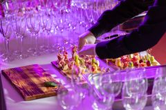The waiter prepared and serves a snack. the buffet at the reception. Assortment of canapes on wooden board. Banquet stock photos