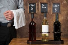 Waiter presents three wine bottles of different price levels Stock Images