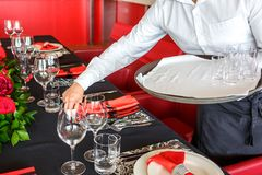 The waiter puts Cutlery on the holiday table royalty free stock photos