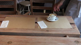 Waiter puts two cups of coffee on the table stock footage
