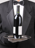 Waiter with Red Wine Bottle Blank Label. Close up of a Waiter holding red wine bottle on silver tray vertical format torso only Stock Images