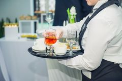 The waiter removes dirty dishes from the tables after guests of the event. Catering Service at business meeting, party, weddings. Royalty Free Stock Photo