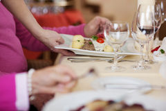 Waiter's Hand Serving Dish To Customers At Restaurant Table. Cropped image of waiter's hand serving dish to customers at restaurant table Stock Image