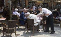 Waiter serving beverages at touristic terrace bar wide view. A waiter seen working on the crowded terraces during the beginning of the summer touristic season in Royalty Free Stock Images