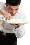 Waiter servant cleaning presenting plate. A male waiter servant or other hospitality staff worker is cleaning and polishing a white plate ready for service stock image