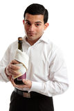 Waiter or servant holding bottle of wine. A waiter or a servant holds a bottle of wine or champagne. White background stock photo
