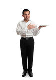 Waiter or servant holding a white plate. Full length smiling male hospitality worker presenting or carrying a whilte plate Stock Image