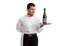 Waiter or servant looking at wine product. A waiter, servant or bartender looking at a wine product on a silver tray and smiling. White background royalty free stock images