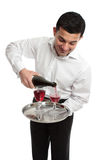 Waiter or servant pouring wine. A waiter or butler pouring sparking red wine into glasses.  White background Royalty Free Stock Photography