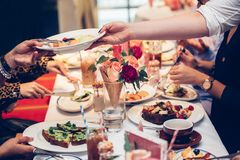Waiter serve the clients table and gives plate with fruit salad on Sunday family brunch. stock photos