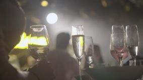 Champagne Glasses on a Tray. Waiter served champagne glasses on a tray in a fine dining restaurant during concert with bright spotlights in the background stock video footage