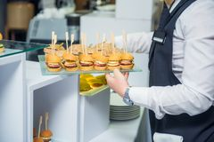The waiter is servering catering buffet table with food and snacks for guests of the event. Dining Food Celebration Party Concept. Royalty Free Stock Photo