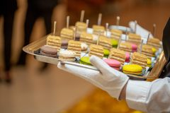 The waiter serves an expensive dessert of macaroons. Macaroon in the restaurant royalty free stock images