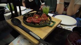 The waiter serves guests paella with seafood and vegetables - a traditional Spanish dish.