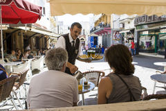A waiter serves milk at Petit Souk Place, Tangier, Morocco Royalty Free Stock Images
