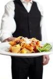 Waiter serves pasta Royalty Free Stock Photos
