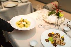 Waiter serves plate of ravioli on table Stock Image
