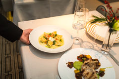 Waiter serves plate of ravioli on table Stock Photography