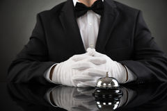 Waiter With Service Bell At Desk Royalty Free Stock Photos