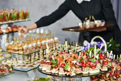 Waiter serving catering table Stock Photography